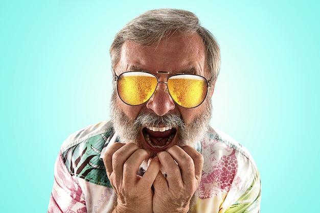 海やアルコールの海を見ながら、軽いビールでいっぱいのサングラスをかけたオクトーバーフェストの年配の男性。顔の表情、びっくり、クレイジー。お祝い、休日、お祭りのコンセプト。彼の目を信じることができない