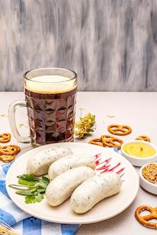 Oktoberfest set. dark beer, weisswurst, pretzels, mustard, spikelets of grain, hop