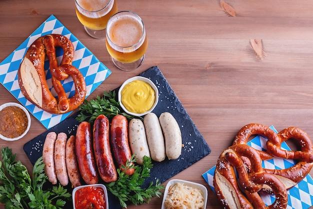 전통 음식이 있는 옥토버페스트 테이블. 구운 소시지, 프레첼, 맥주, 신 양배추, 나무 배경에 겨자, 위쪽 전망, 복사 공간, 웹 배너