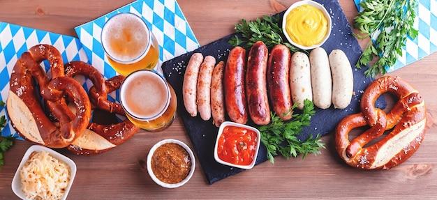伝統的な料理のオクトーバーフェストテーブル。ローストソーセージ、プレッツェル、ビール、酸っぱいキャベツ、木製の背景にマスタード、上面図、コピースペース、ウェブバナー