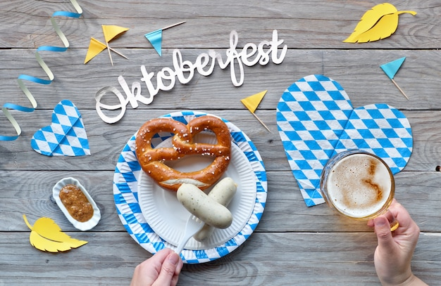 Oktoberfest, traditional festival food: white sausages, pretzel and beer. flat lay on rustic wooden table with blue and white checkered decorations and yellow autumn leaves