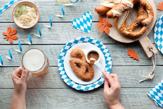 オクトーバーフェストの伝統的な食べ物、青と白の紙の装飾が施された木製のテーブルの上に平らに置かれました。