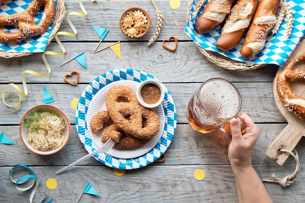 Oktoberfest traditional food, flat lay on wooden table with blue and white bavarian decorations.