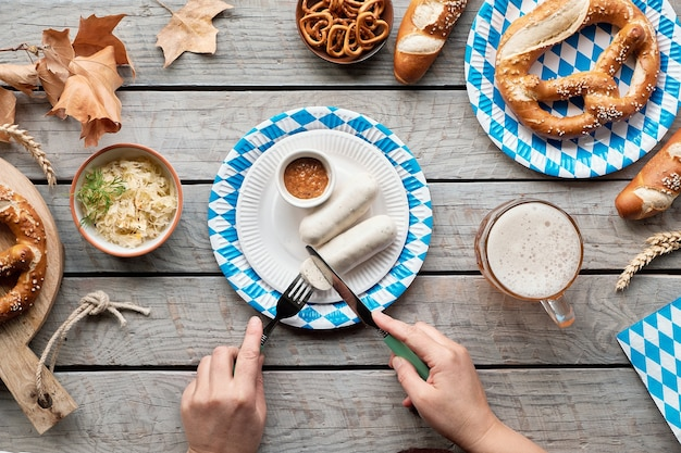 Oktoberfest traditional food, flat lay on wooden table with blue and white paper decorations.