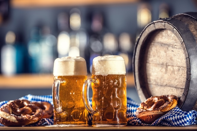 Oktoberfest two large beer with pretzel wooden barrel and blue tablecloth.