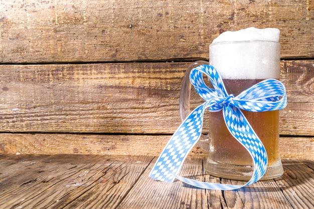 옥토버페스트에서는 프레첼, 밀, 홉을 곁들인 다양한 맥주 잔과 머그잔. 바와 펍 메뉴, 나무 배경 복사 공간에 초대 카드 배경
