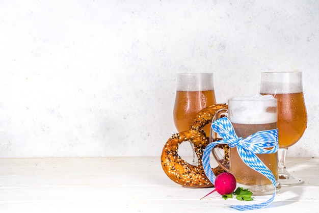 Oktoberfest various beer glasses and mugs with pretzel, wheat and hops. bar and pub menu, invitation card background on white wooden background copy space