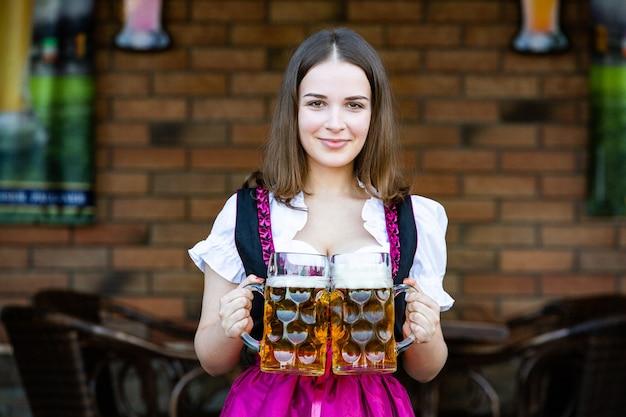 ビールジョッキを保持している伝統的なバイエルンのドレスを着ているオクトーバーフェストの女性