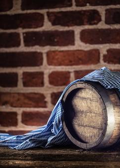 Oktoberfest wooden barrel and blue tablecloth on rustic oak table.