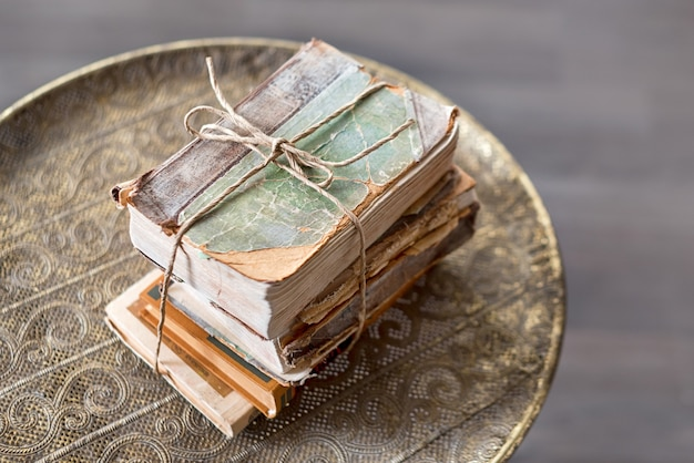 Old 100 years books on antique table closeup, history, knowledge, nostalgia, old age concept.