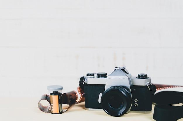 古い35mm一眼レフフィルムカメラと木製の背景にフィルムのロール。フリム写真のコンセプト。
