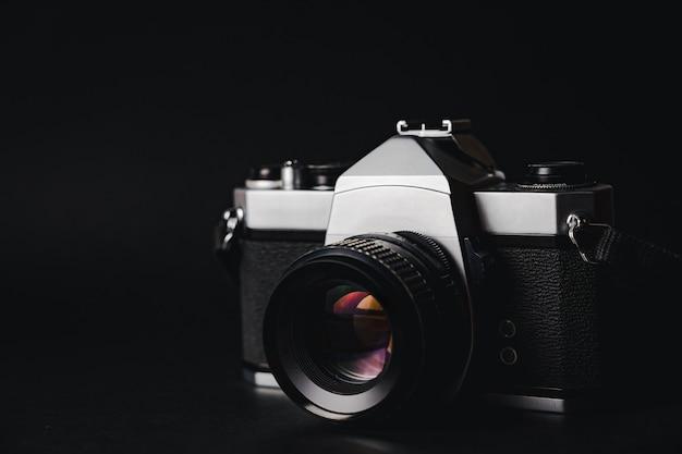 黒の背景に古い35mm一眼レフフィルムカメラ。フリム写真のコンセプト。