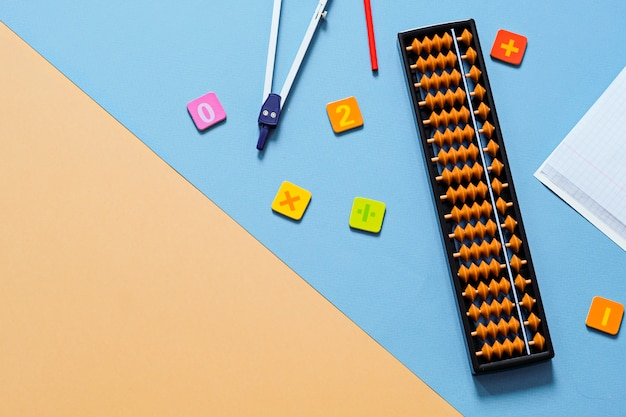 Old abacus with school supplies, drawing compass . mental mathematics, math concept.