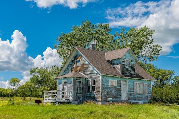 Kayville, 서스 캐처 원, 캐나다에있는 나무, 잔디와 푸른 하늘이있는 오래 된 버려진 푸른 대초원 농가