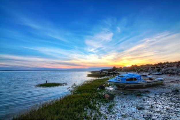 背景の美しい海の景色に古い放棄されたボート。