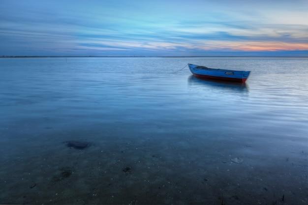海の風景の背景に海に古い放棄された船。
