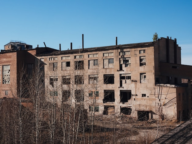 An old abandoned factory building in early autumn. post-apocalyptic background. collapsing buildings.