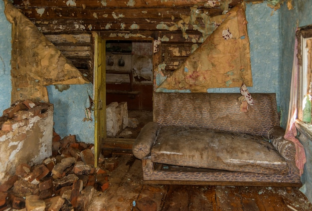 Old abandoned farmhouse. the sofa in the room. ruin and dirt