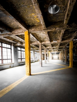 Old abandoned hallway with big windows at factory