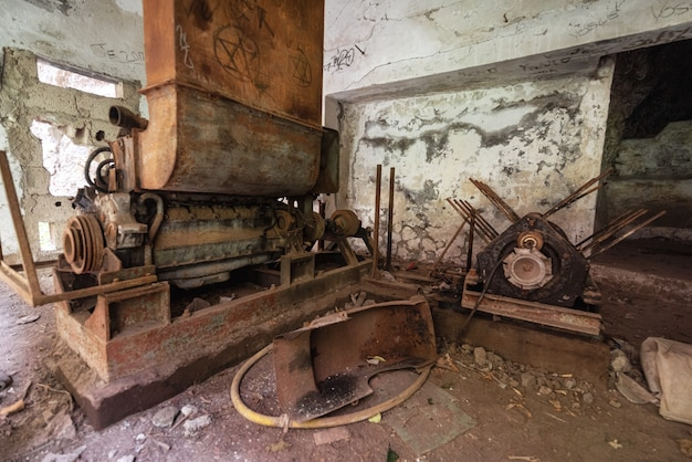 Old abandoned industrial machine tools and rusty metal equipment in abandoned factory.
