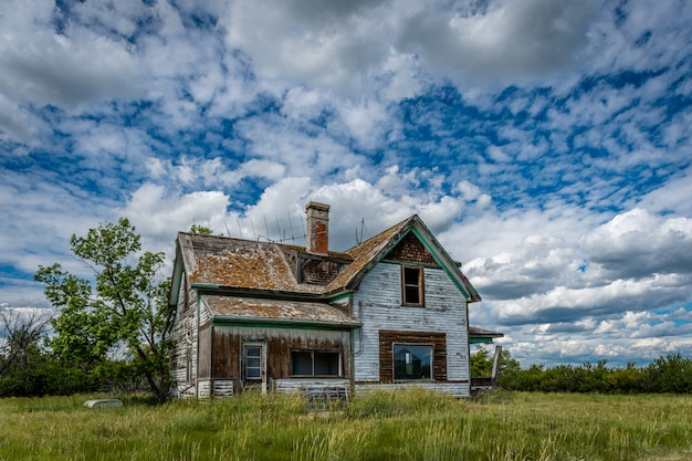 Old, abandoned prairie farmhouse with trees