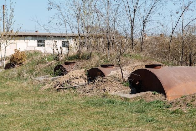 오래 된 버려진 녹슨 배럴은 땅에 반쯤 묻혀있다