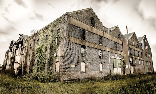 Old abandoned stone building with broken windows under the dark cloudy sky