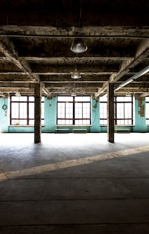 Old abandoned warehouse at factory with long hallway and big windows