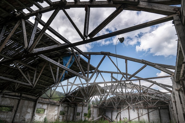 Old abandoned warehouse hangar with a ruined leaky roof and wooden floors, overgrown with grass inside.
