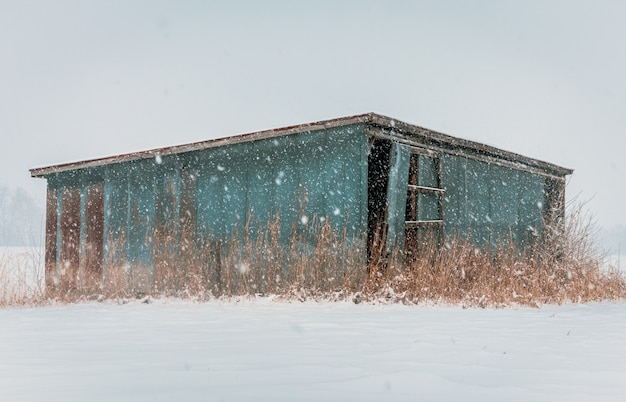 Old abandoned wooden blue hut in a deserted area during the snow storm