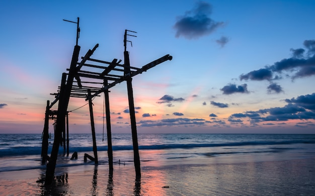 Old abandoned wooden bridge with seascape sunset sky