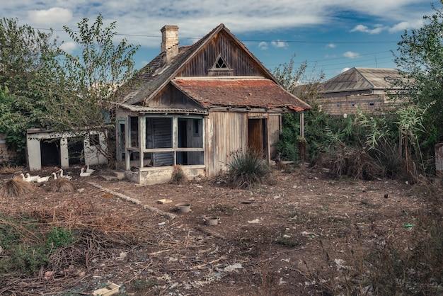古い放棄された木造の田舎の家と庭