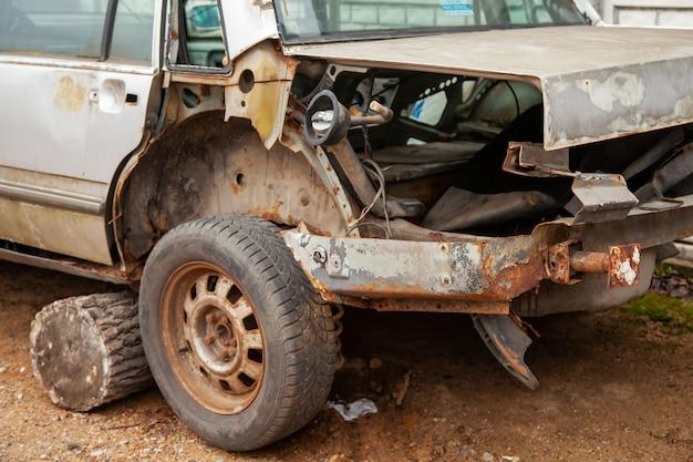 古い放棄された大破した車。不明な量産メーカーの分解した乗用車の裏