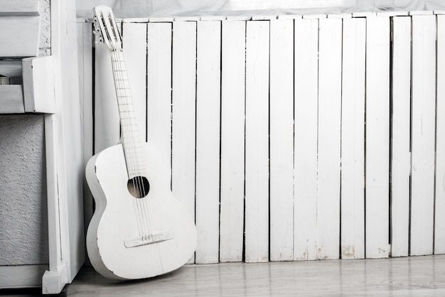Old acoustic guitar leaning against the white wooden wall