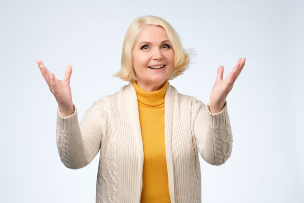 Old adult blonde excited cheerful astonished lady smiling, laughing