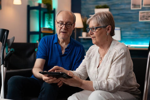 집에서 소파에 디지털 태블릿을 들고 있는 노부부