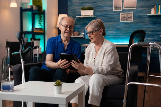 Old adult couple holding digital tablet at home on couch using modern technology for entertainment and online internet communication. elder man and woman with crutches and walk frame