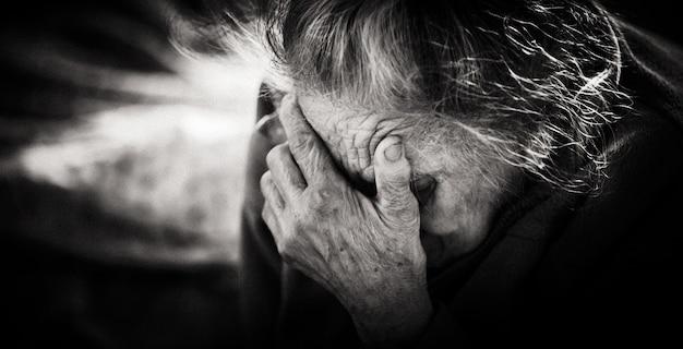 Концепция старости. черно-белый портрет очень старой и усталой морщинистой женщины. очень старый седой портрет крупным планом лицо женщины. стилизация старых фотографий, добавлена зернистость пленки. тонированная сепия. винтаж, ретро стиль