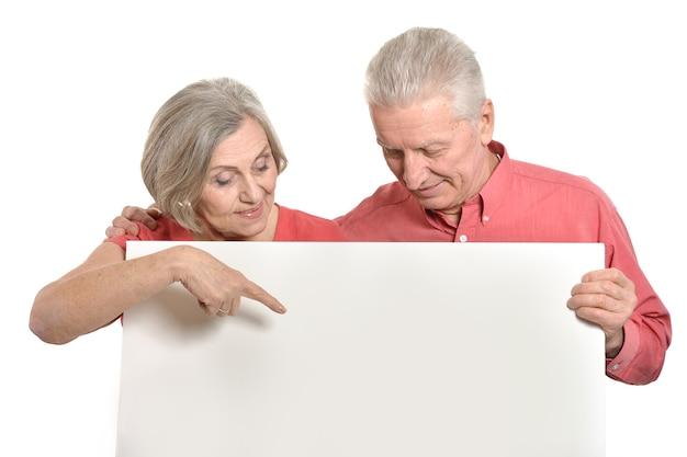 白い背景に対して空白のバナー広告を保持している老夫婦