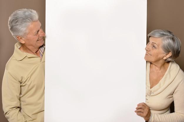 空白のバナーと白い背景を保持している老夫婦
