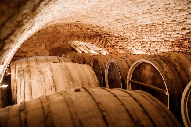 이탈리아, 포르토, 포르투갈, 프랑스의 시원하고 어두운 지하실에 줄지어 있는 금고에 와인을 넣은 오래된 전통 나무 통