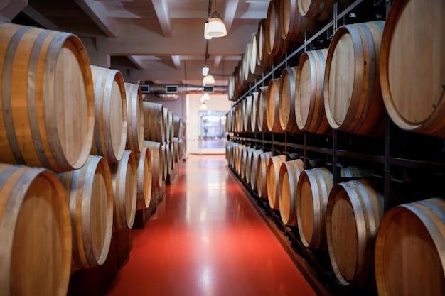 Старые традиционные деревянные бочки с вином в хранилище выстроились в прохладном и темном погребе в италии, порту, португалии, франции
