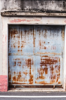 Old aged vintage rusty red brown textured zinc alloy metal sheet exterior fence door of warehouse