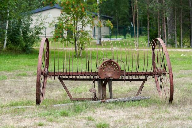 Старая сельскохозяйственная техника с большими колесами в сельском дворе. заброшенный старый и ржавый плуг