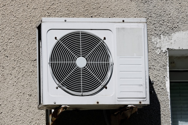 Old air conditioner hangs on the wall of a residential building. high quality photo