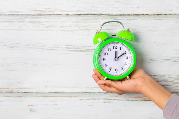 Old alarm clock alarm in hand of girl