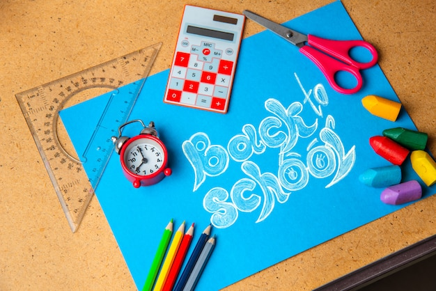 Old alarm clock on the background with school supplies.
