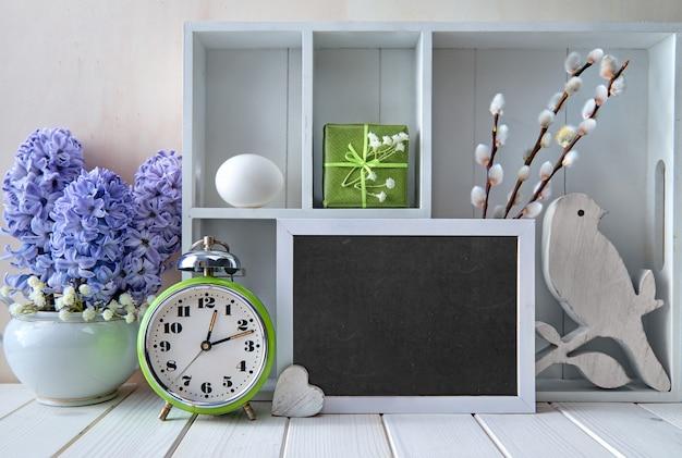 Старый будильник, синие цветы гиацинта и витрина с различными предметами. мел текст
