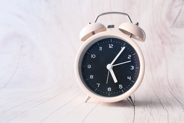 木製の背景に古い目覚まし時計。