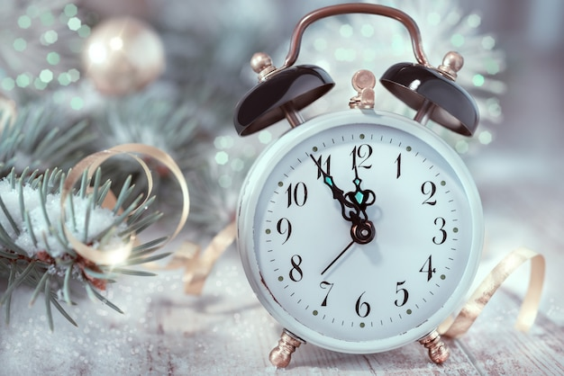 Old alarm clock showing five to midnight. happy new year!